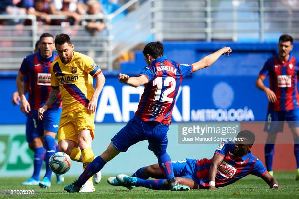 Lionel Messi of FC Barcelona being followed by Paulo Oliveira and Papakouli Diop of SD Eibar during the Liga match between SD Eibar SAD and FC...