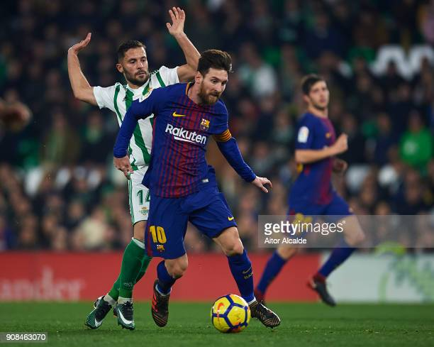 Lionel Messi of FC Barcelona being followed by Riza Durmisi of Real Betis Balompie the La Liga match between Real Betis and Barcelona at Estadio...