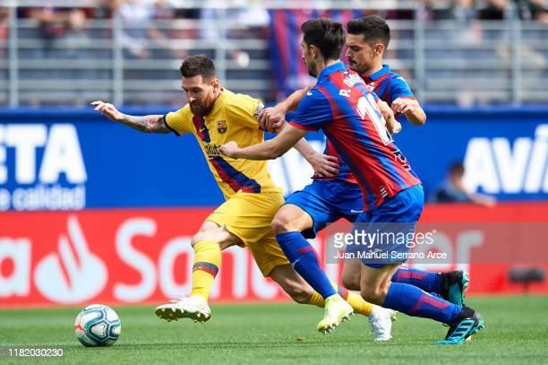 Lionel Messi of FC Barcelona being followed by Sergio Alvarez of SD Eibar and Paulo Oliveira of SD Eibar during the Liga match between SD Eibar SAD...