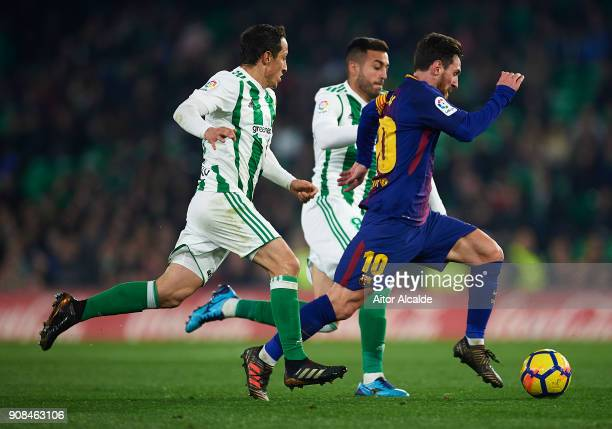 Lionel Messi of FC Barcelona being followed by Victor Camarasa of Real Betis Balompie and Andres Guardado of Real Betis Balompie the La Liga match...