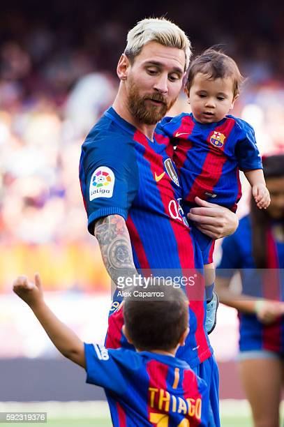 Lionel Messi of FC Barcelona carries his son Mateo Messi as he speaks to his son Thiago Messi before the La Liga match between FC Barcelona and Real...