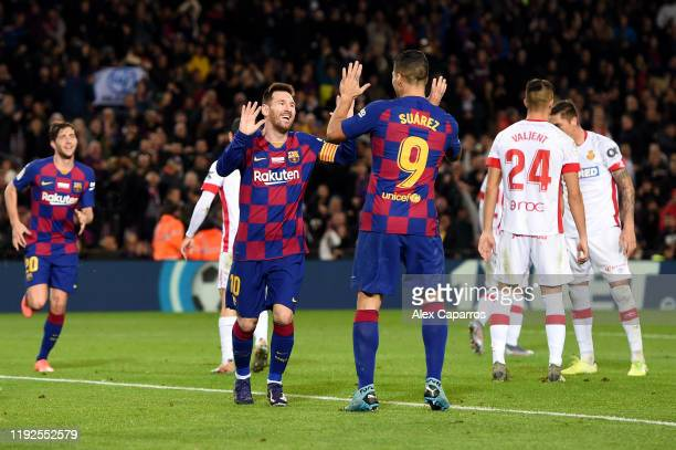 Lionel Messi of FC Barcelona celebrates after scoring his team's fifth goal with Luis Suarez of FC Barcelona during the Liga match between FC...