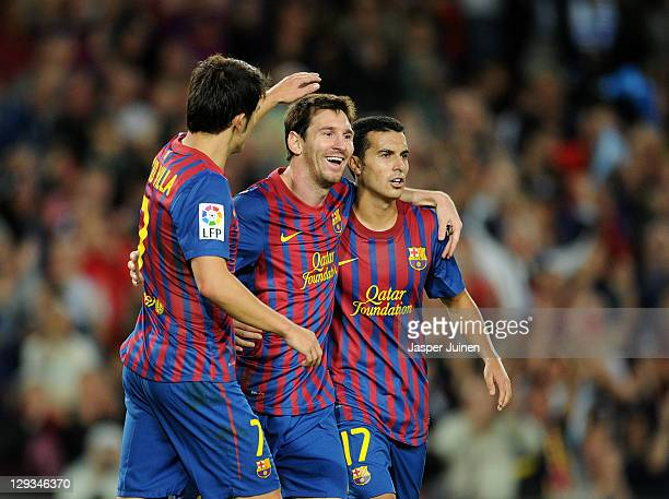 Lionel Messi of FC Barcelona celebrates scoring his second goal with his teammates Pedro Rodriguez and David Villa during the la Liga match between...