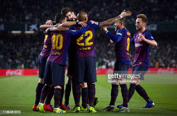 Lionel Messi of FC Barcelona celebrates scoring his team's opening goal with team mates during the La Liga match between Real Betis Balompie and FC...