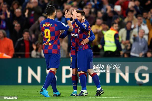 Lionel Messi of FC Barcelona celebrates scoring his team's third goal with teammates Luis Suarez and Antoine Griezmann during the La Liga match...
