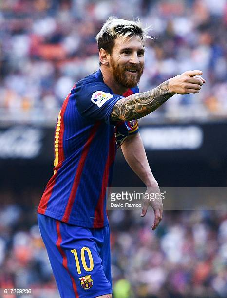 Lionel Messi of FC Barcelona celebrates towards a TV camera after scoring his team's third from the penalty spot during the La Liga match between...
