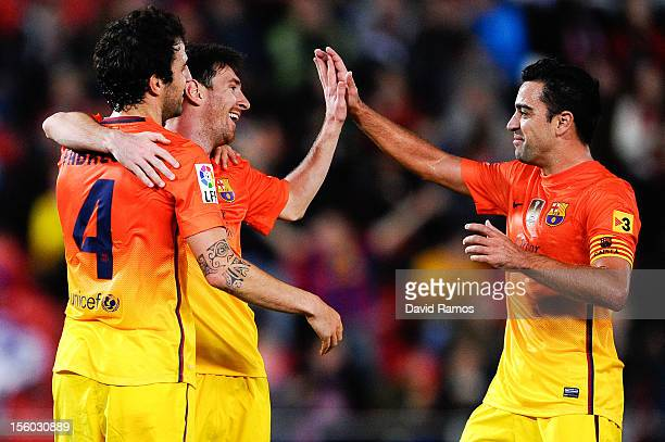 Lionel Messi of FC Barcelona celebrates with Cesc Fabregas and Xavi Hernandez of FC Barcelona after scoring his team's second goal during the La Liga...