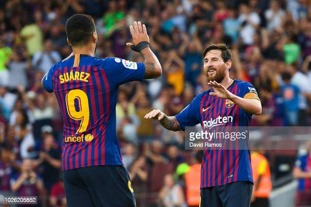 Lionel Messi of FC Barcelona celebrates with his team ate Luis Suarez after scoring his team's sixth goal during the La Liga match between FC...