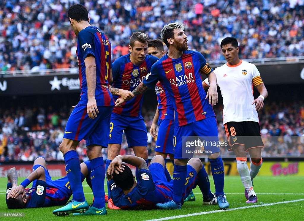 Lionel Messi of FC Barcelona celebrates with his team mates as Neymar Jr. and Luis Suarez reacts on the pitch after being hit by objects thrown from the seats after scoring his team's third from the penalty spot during the La Liga match between Valencia CF and FC Barcelona at Mestalla stadium on October 22, 2016 in Valencia, Spain.