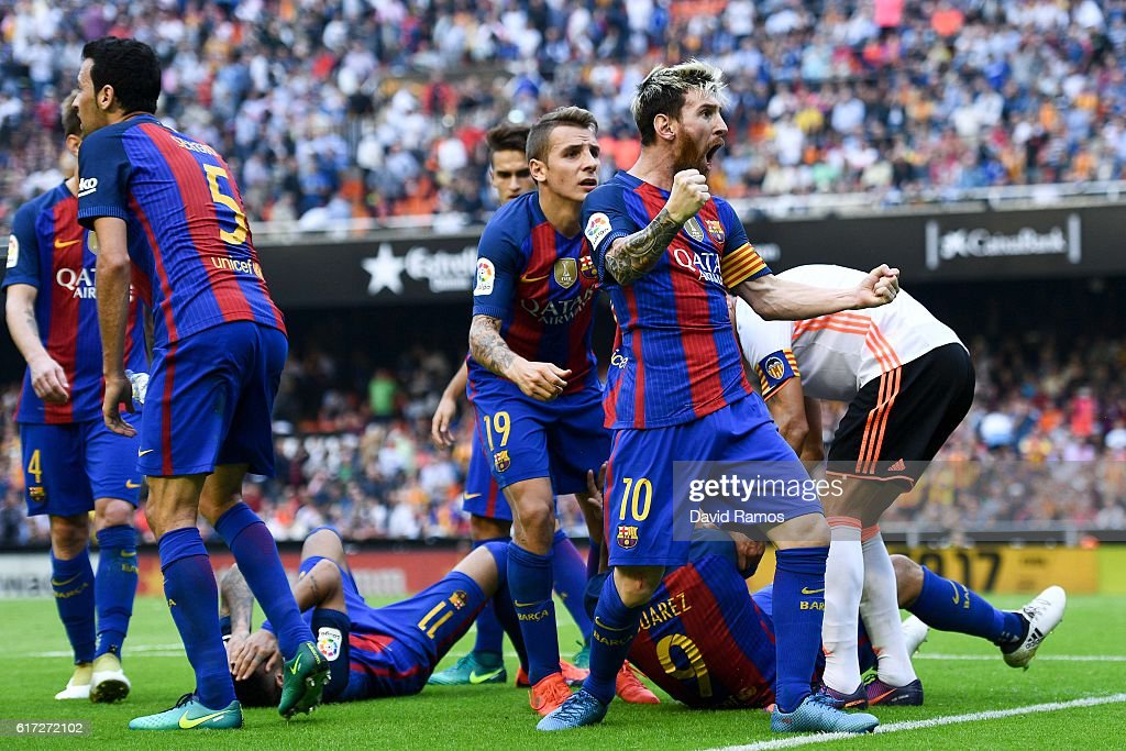Lionel Messi of FC Barcelona celebrates with his team mates as Neymar Jr. and Luis Suarez reacts on the pitch after being hit by objects thrown from the seats after scoring his team's third from the penalty spot goal during the La Liga match between Valencia CF and FC Barcelona at Mestalla stadium on October 22, 2016 in Valencia, Spain.