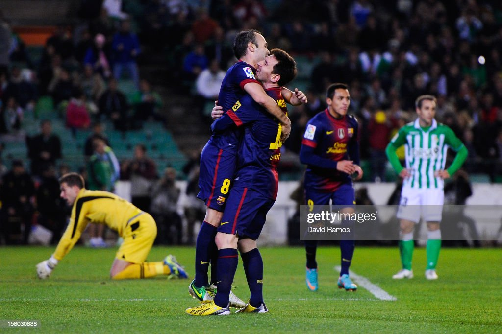 Lionel Messi of FC Barcelona celebrates with his team-mate Andres Iniesta of FC Barcelona after scoring his team's second goal during the La Liga match between Real Betis Balompie and FC Barcelona at Estadio Benito Villamarin on December 9, 2012 in Seville, Spain. With this goal Lionel Messi beats the 1972 scoring record set by Gerd Muller of 85 goals in one year.