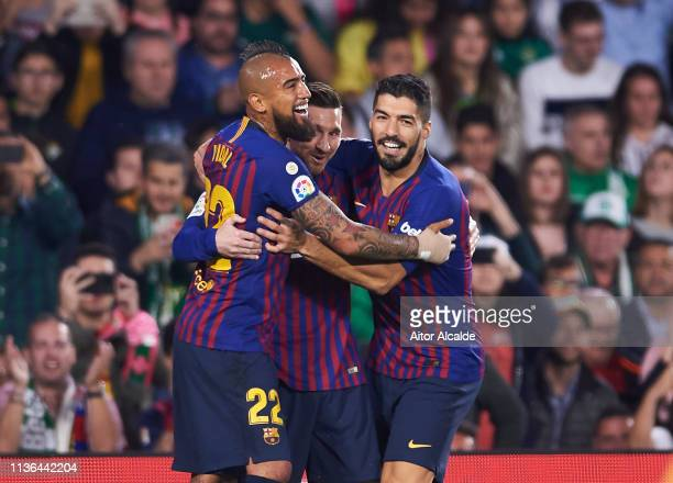 Lionel Messi of FC Barcelona celebrates with his teammate Arturo Vidal and Luis Suarez of FC Barcelona after scoring the opening goal during the La...