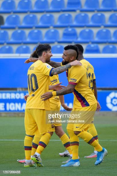 Lionel Messi of FC Barcelona celebrates with his teammate Arturo Vidal after scoring his sides fifth goal during the Liga match between Deportivo...