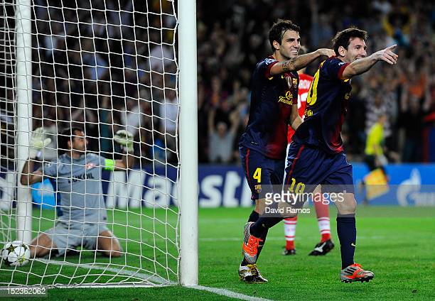 Lionel Messi of FC Barcelona celebrates with his teammate Cesc Fabregas after scoring his team's third goal during the UEFA Champions League Group G...