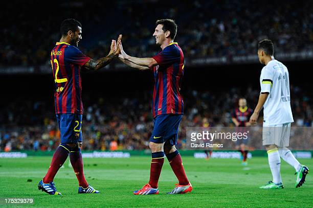 Lionel Messi of FC Barcelona celebrates with his team-mate Dani Alves of FC Barcelona after scoring his team's second goal during a friendly match...