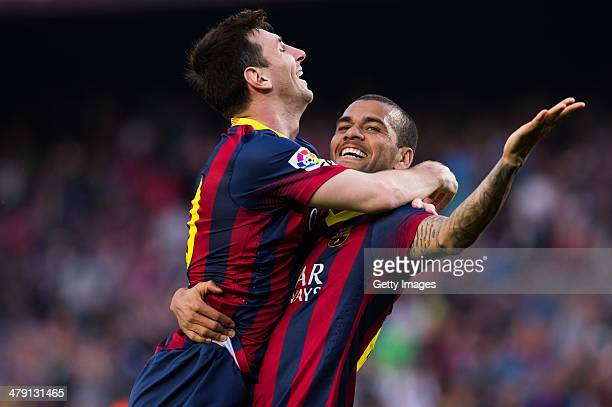 Lionel Messi of FC Barcelona celebrates with his teammate Daniel Alves after scoring his team's sixth goal during the La Liga match between FC...