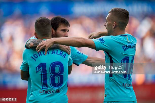 Lionel Messi of FC Barcelona celebrates with his teammate Jordi Alba and Gerard Deulofeu of FC Barcelona after scoring the opening goal during the La...
