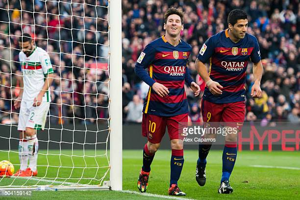 Lionel Messi of FC Barcelona celebrates with his teammate Luis Suarez after scoring his team's third goal during the La Liga match between FC...