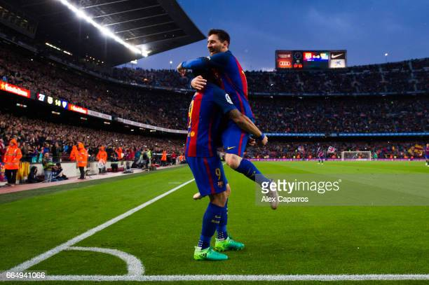 Lionel Messi of FC Barcelona celebrates with his teammate Luis Suarez after scoring his team's second goal during the La Liga match between FC...