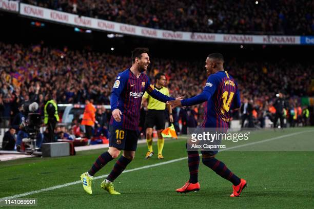 Lionel Messi of FC Barcelona celebrates with his teammate Malcom after scoring his team's second goal during the La Liga match between FC Barcelona...