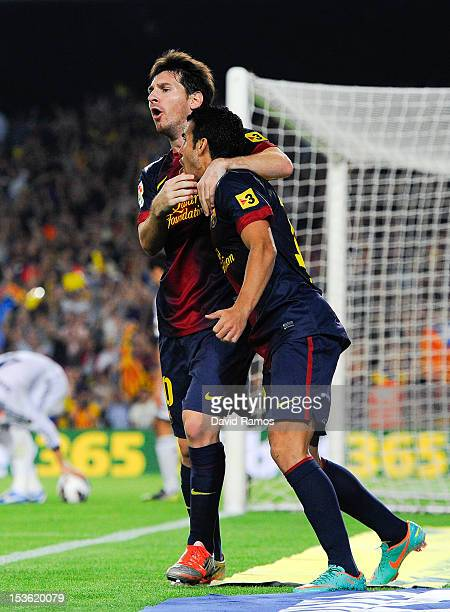 Lionel Messi of FC Barcelona celebrates with his teammate Pedro Rodriguez after scoring his team's first goal during the La Liga match between FC...