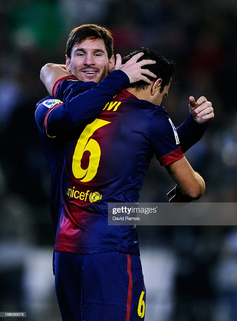 Lionel Messi of FC Barcelona (R) celebrates with his teammate Xavi Hernandez of FC Barcelona after scoring his team's second goal the La Liga match between Real Betis Balompie and FC Barcelona at Estadio Benito Villamarin on December 9, 2012 in Seville, Spain. With this goal Lionel Messi beats the 1972 scoring record set by Gerd Muller of 85 goals in one year.