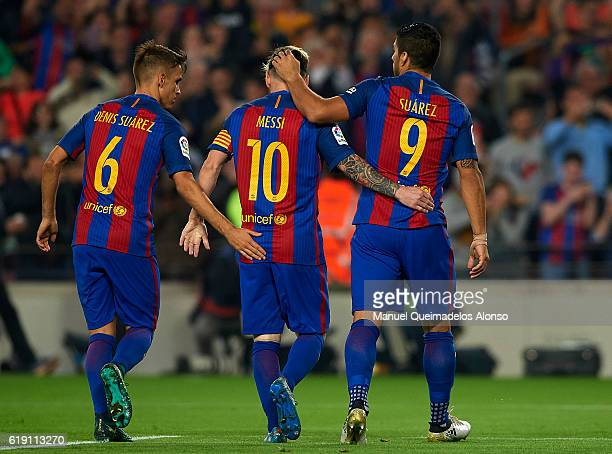 Lionel Messi of FC Barcelona celebrates with his teammates Denis Suarez and Luis Suarez during the La Liga match between FC Barcelona and Granada at...