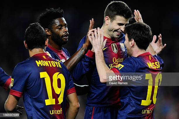 Lionel Messi of FC Barcelona celebrates with his teammates Gerard Pique and Alex Song after scoring the opening goal during the La Liga match between...