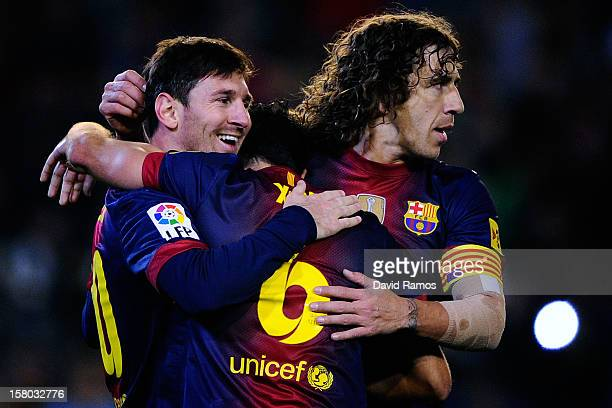 Lionel Messi of FC Barcelona celebrates with his teammates Xavi Hernandez and Carles Puyol of FC Barcelona after scoring his team's second goal the...