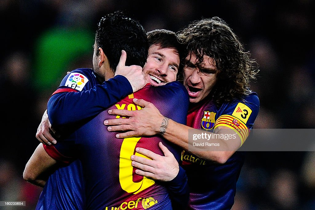 Lionel Messi (C) of FC Barcelona celebrates with his teammates Xavi Hernandez (L) and Carles Puyol after scoring the opening goal during the La Liga match between FC Barcelona and CA Osasuna at Camp Nou on January 27, 2013 in Barcelona, Spain.