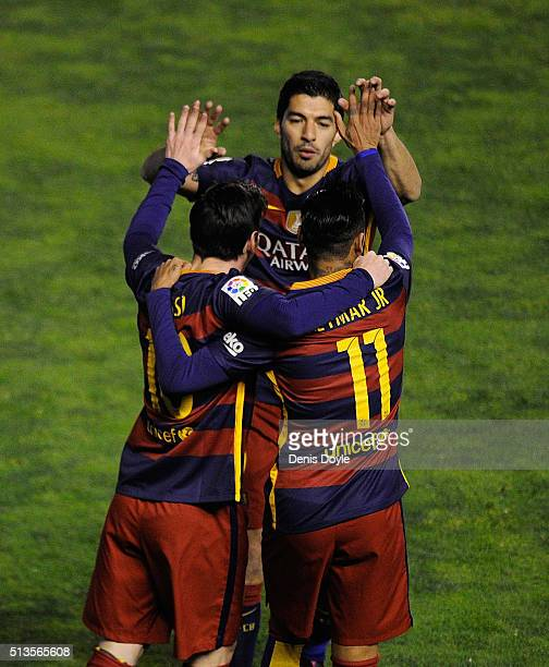 Lionel Messi of FC Barcelona celebrates with Luis Suarez and Neymar after scoring his team's 2nd goal during the La Liga match between Rayo Vallecano...