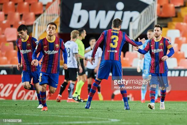 Lionel Messi of FC Barcelona celebrates with team mate Gerard Pique after scoring their side's first goal during the La Liga Santander match between...