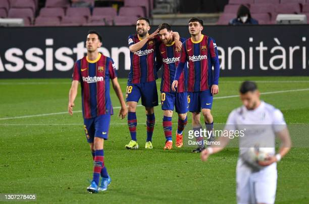 Lionel Messi of FC Barcelona celebrates with team mates Jordi Alba and Pedri after scoring their side's first goal during the La Liga Santander match...