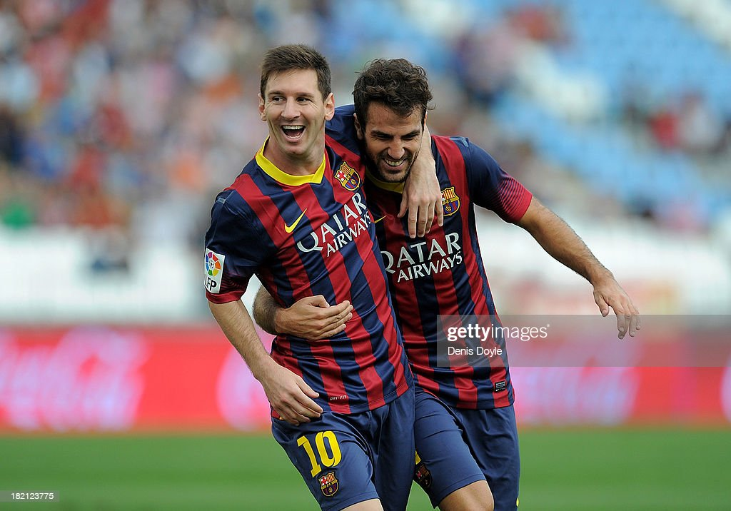 Lionel Messi (L) of FC Barcelona celebrates with team-mate Cesc Fabregas after scoring the opening goal during the La Liga match between UD Almeria and FC Barcelona on September 28, 2013 in Almeria, Spain.