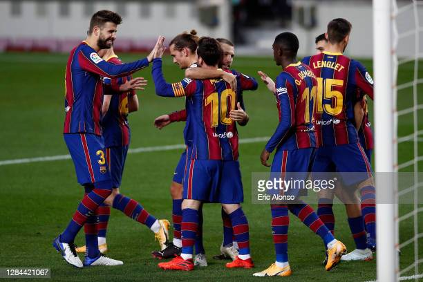Lionel Messi of FC Barcelona celebrates with teammates after scoring his team's third goal during the La Liga Santader match between FC Barcelona and...