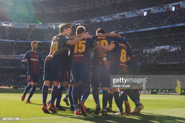 Lionel Messi of FC Barcelona celebrates with teammates after scoring his team's 2nd goal during the La Liga match between Real Madrid and Barcelona...