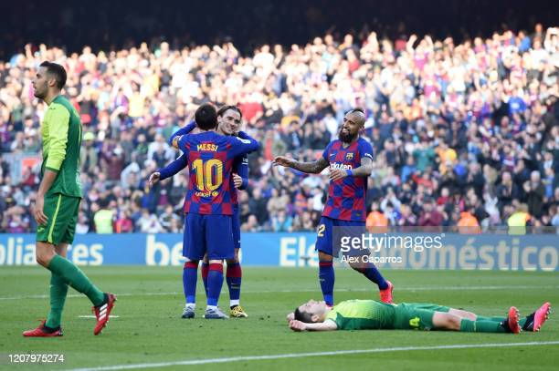Lionel Messi of FC Barcelona celebrates with teammates Antoine Griezmann and Arturo Vidal after scoring his team's third goal during the La Liga...