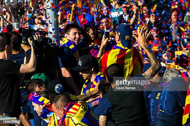 Lionel Messi of FC Barcelona celebrates with teammates on an open top bus during their victory parade after winning the Spanish Liga title on May 13...