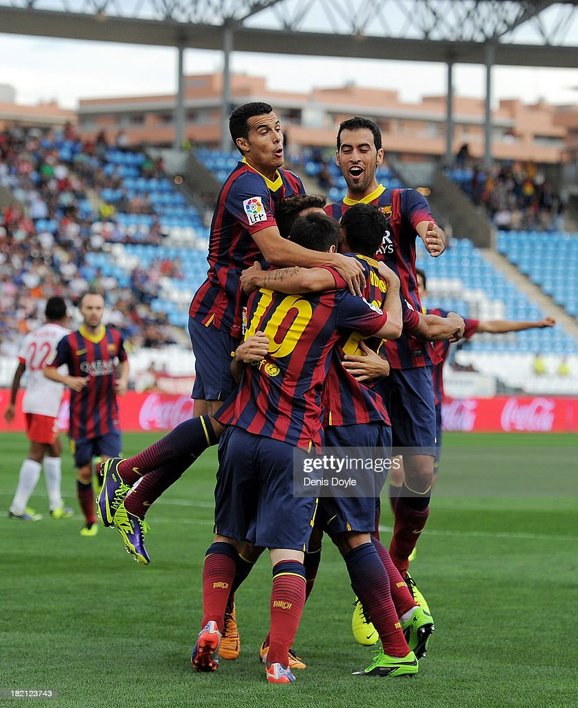 Lionel Messi (#10) of FC Barcelona celebrates with team-mates Pedro Rodriguez (L) and Sergio Busquets after scoring the opening goal during the La Liga match between UD Almeria and FC Barcelona on September 28, 2013 in Almeria, Spain.
