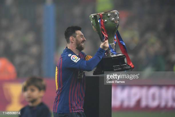 Lionel Messi of FC Barcelona celebrates with the La Liga trophy following his team's victory in the La Liga match between FC Barcelona and Levante UD...