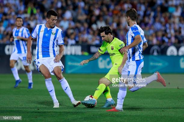 Lionel Messi of FC Barcelona cob Ruben Perez and his teammate Mikel Vesga during the La Liga match between CD Leganes and FC Barcelona at Estadio...
