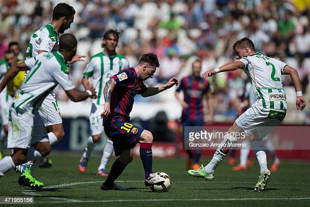 Lionel Messi of FC Barcelona competes for the ball with Aleksandar Pantic of Cordoba CF during the La Liga match between Cordoba CF and Barcelona FC...