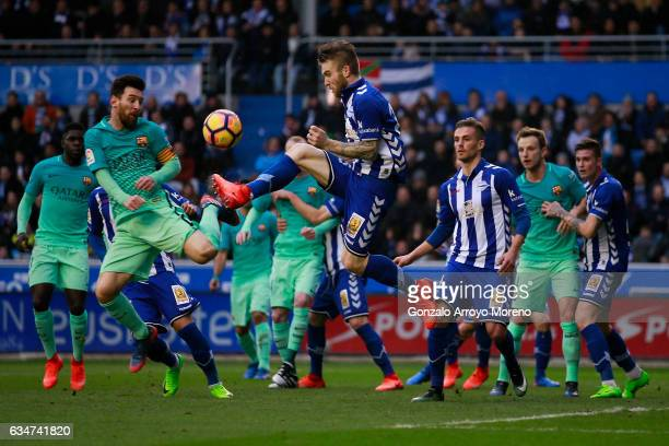 Lionel Messi of FC Barcelona competes for the ball with Aleksandar Katai of Deportivo Alaves during the La Liga match between Deportivo Alaves and FC...