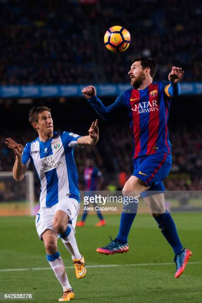 Lionel Messi of FC Barcelona competes for the ball with Alexander Szymanowski of CD Leganes during the La Liga match between FC Barcelona and CD...
