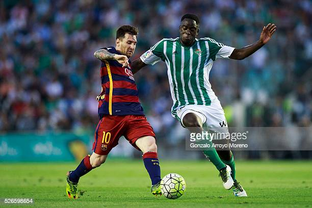 Lionel Messi of FC Barcelona competes for the ball with Alfred N Diaye of Real Betis Balompie during the La Liga match between Real Betis Balompie...