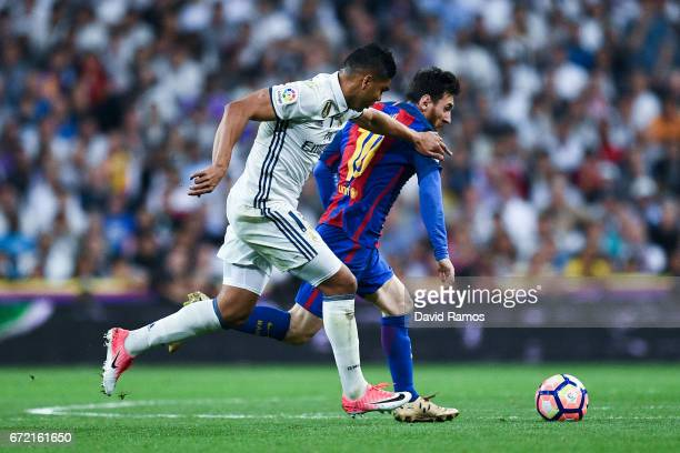 Lionel Messi of FC Barcelona competes for the ball with Carlos Enrique Casimiro of Real Madrid CF during the La Liga match between Real Madrid CF and...