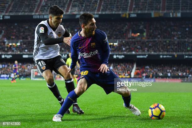 Lionel Messi of FC Barcelona competes for the ball with Carlos Soler of Valencia CF during the La Liga match between Valencia and Barcelona at...