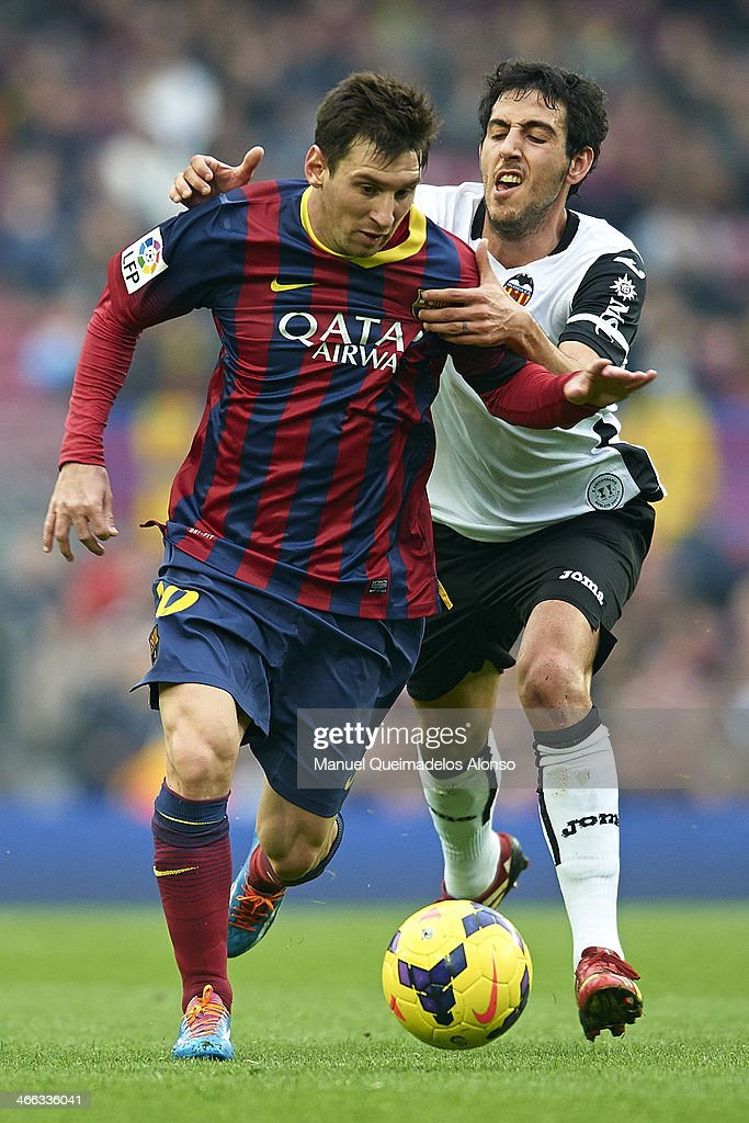 Lionel Messi of FC Barcelona competes for the ball with Dani Parejo (R) of Valencia CF during the La Liga match between FC Barcelona and Valencia CF at Camp Nou on February 1, 2014 in Barcelona, Spain.