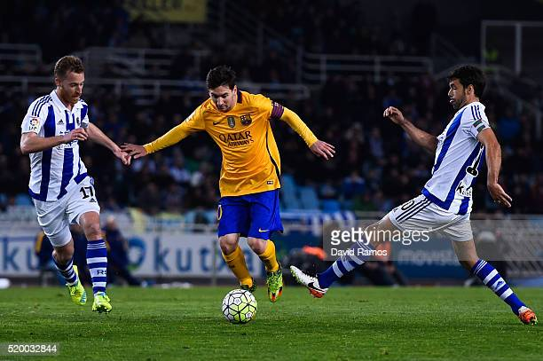Lionel Messi of FC Barcelona competes for the ball with David Zurutuza Veillet and Xabier Prieto Argarate of Real Sociedad the La Liga match between...