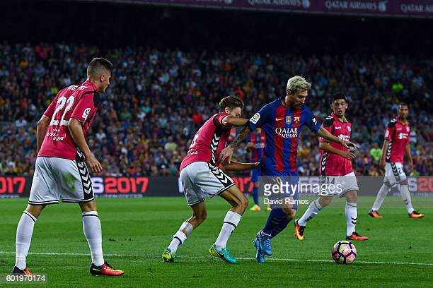 Lionel Messi of FC Barcelona competes for the ball with Deportivo Alaves players during the La Liga match between FC Barcelona and Deportivo Alaves...
